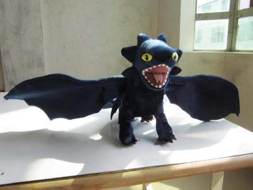 На картинке мягкая игрушка большой дракон Беззубик (Ночная фурия) дышит огнем, вид спереди.