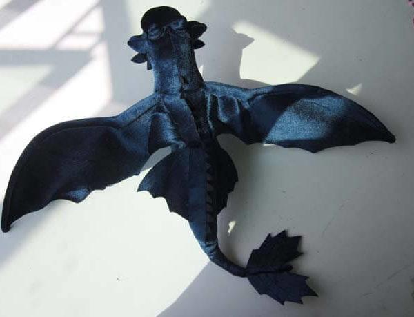 На картинке мягкая игрушка большой дракон Беззубик (Ночная фурия) дышит огнем, вид сверху.