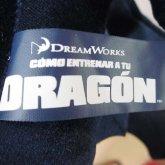 На картинке мягкая игрушка большой дракон Беззубик (Ночная фурия) дышит огнем, детали.