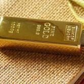 На картинке золотая флешка в виде слитка золота, общий вид.