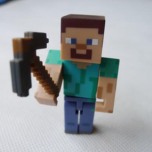 На картинке фигурка Стива из Майнкрафт с киркой (Minecraft STEVE), вид спереди.