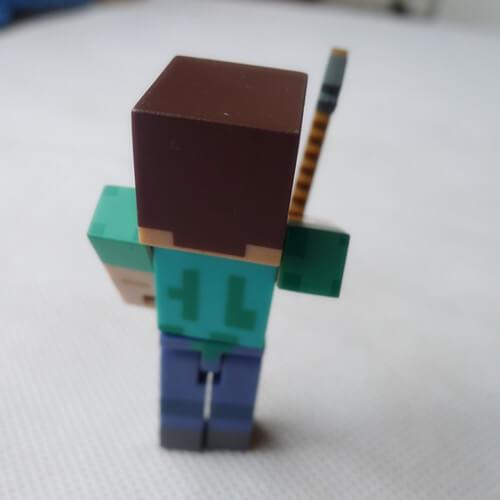 На картинке фигурка Стива из Майнкрафт с киркой (Minecraft STEVE), вид сзади.