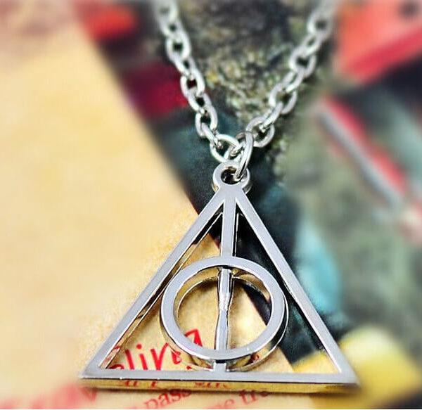 На картинке кулон-подвеска со знаком «Даров смерти» (Гарри Поттер), цвет серебряный, крупный план.