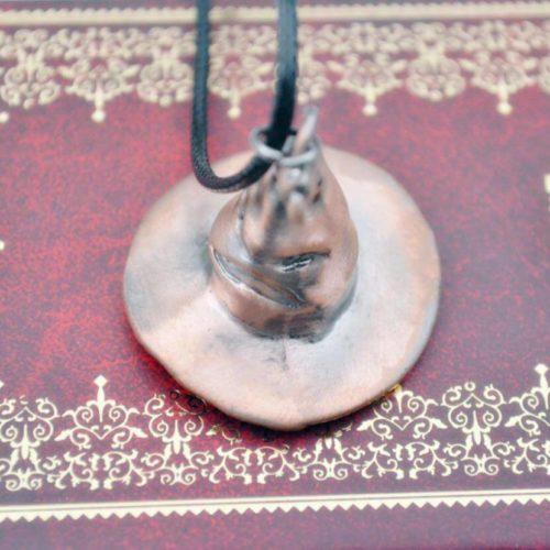 На картинке кулон-подвеска говорящая распределяющая шляпа из Гарри Поттера, крупный план.