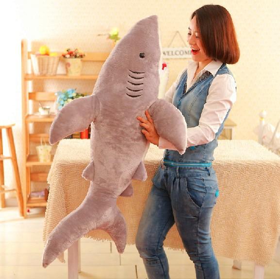 На картинке мягкая плюшевая игрушка акула, вид сбоку.