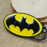 На картинке брелок «Бэтмен», крупный план, цвет желтый.