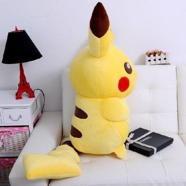 На картинке плюшевая игрушка Пикачу (Покемон), вид сбоку.