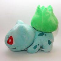 На картинке мягкая игрушка покемон Бульбазавр (Bulbasaur), вид сбоку.