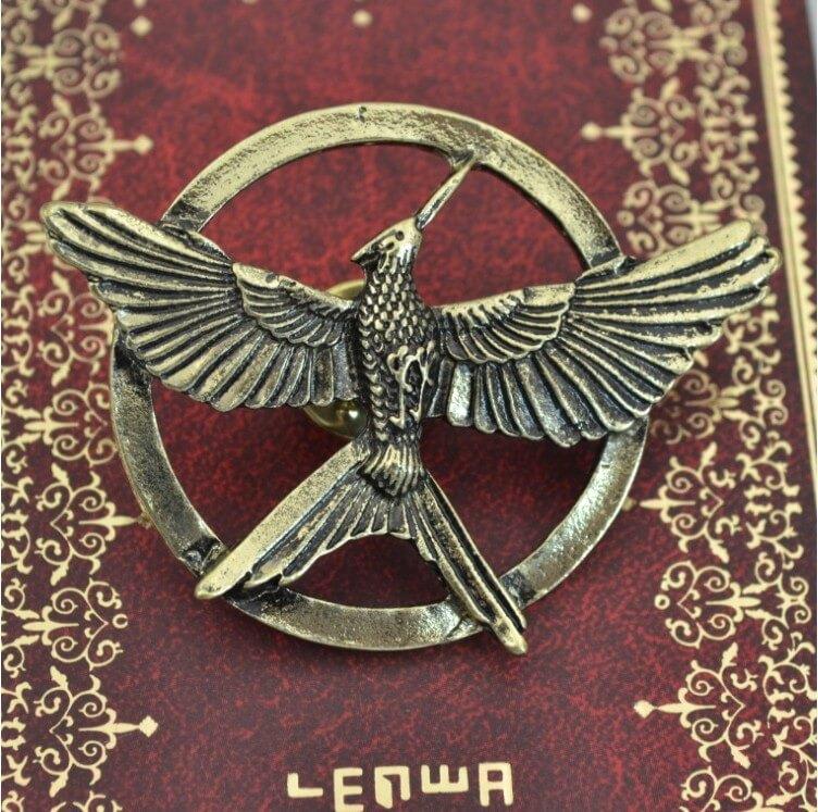 На картинке значок «Сойка пересмешница» (Голодные игры), вариант Бронза.