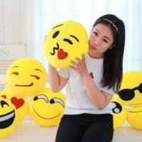 На картинке плюшевые подушки смайлики emoji (12 вариантов).