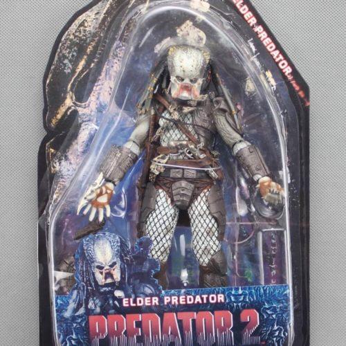На картинке коллекционная фигурка Хищник 2 Старейшина (Predator neca \ Нека), вид спереди в упаковке.